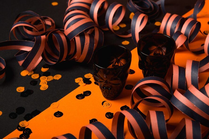Skull-shaped glass cups with black and orange ribbon
