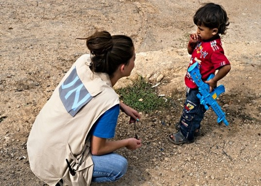 UNHCR worker talking to Syrian child